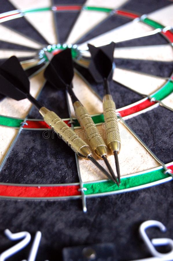Darts on a Dartboard. Three black and gold darts laying on a new dartboard stock photography