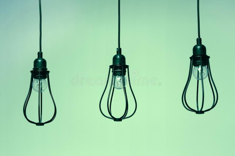 Three black incandescent light bulbs on green background. royalty free stock photo