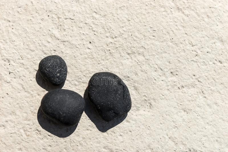 Three black pebbles on a white surface. Black and white background stock photo