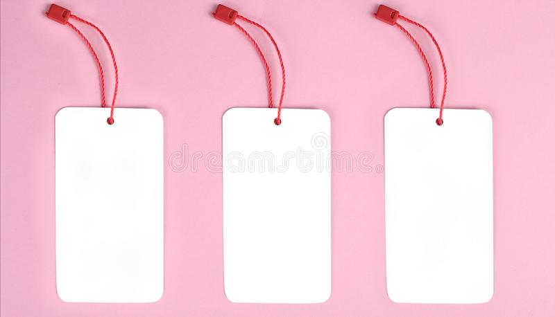 Three blank decorative cardboard tag with red twine tie, on pink background. Mock up royalty free stock images