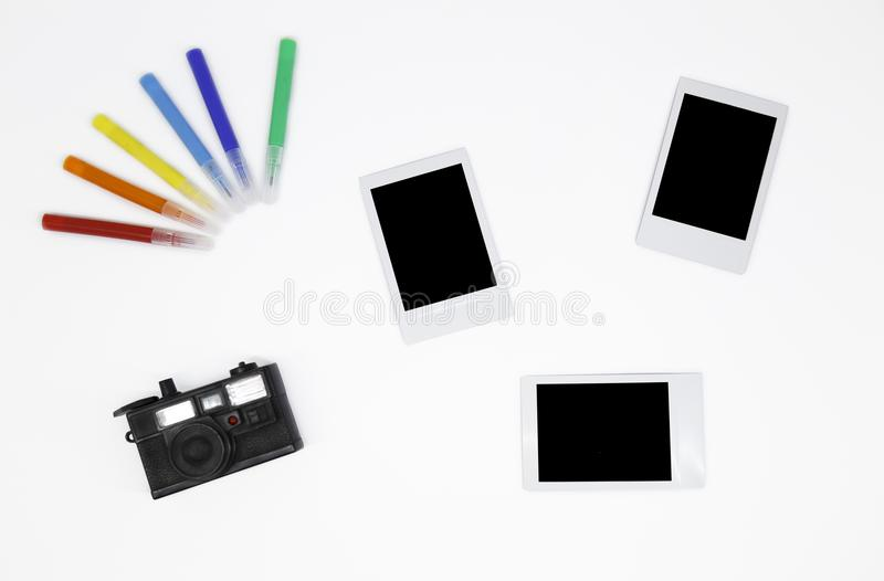 `Three blank instant photos frames with a mini camera and colorful markers ` royalty free stock images