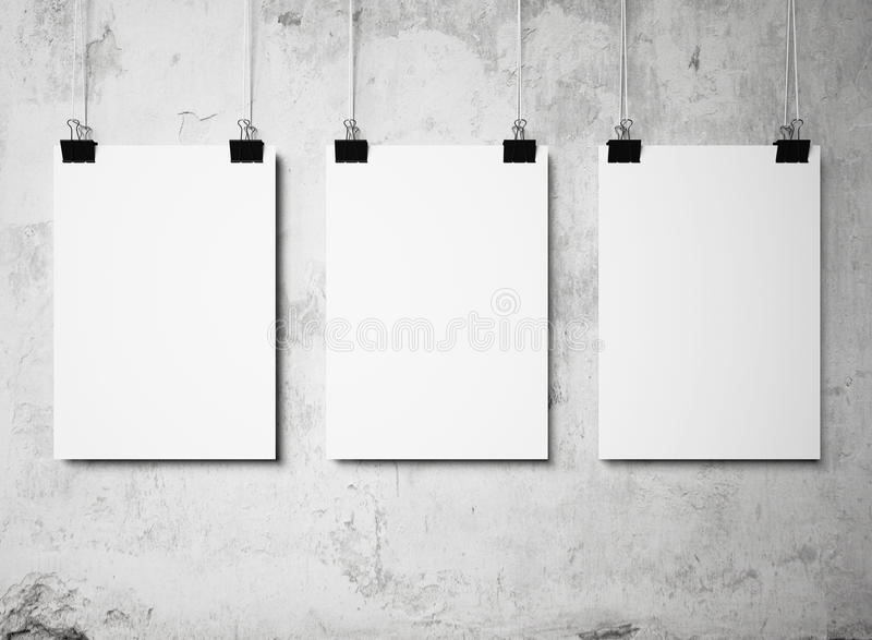 Three blank poster hanging on a white background painted walls royalty free stock photo