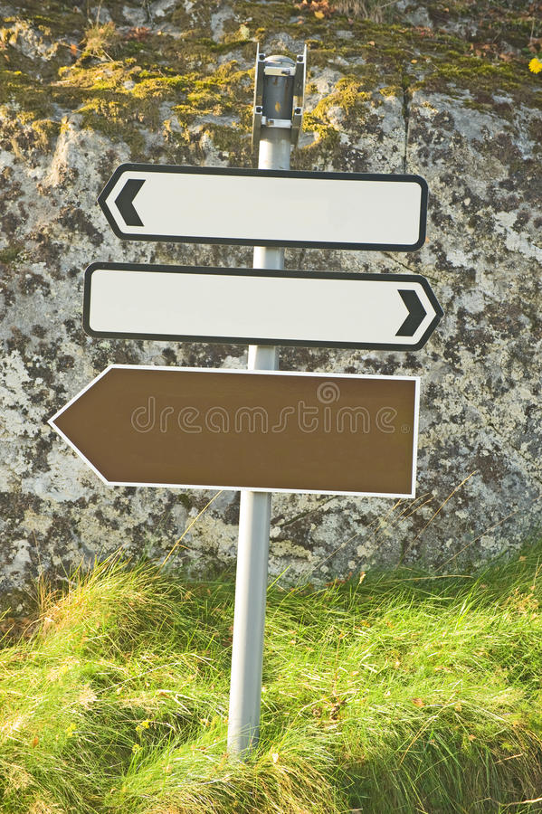 Three blank road signs. An image of two blank white and one blank brown road signs set against a rock and grass verge royalty free stock photography