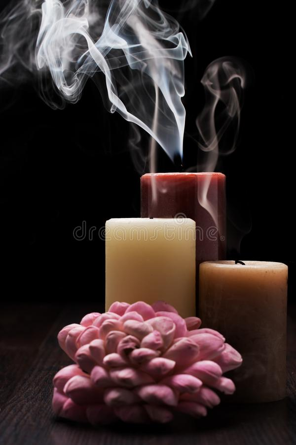 Three candles with smoke on wooden table with black background and a pink flower arrangment. Rembrandt lighting inspired Christmas royalty free stock photos