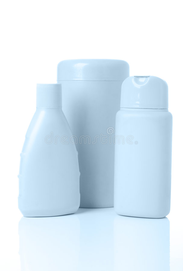 Three blue cosmetics bottle. With reflection on white royalty free stock images