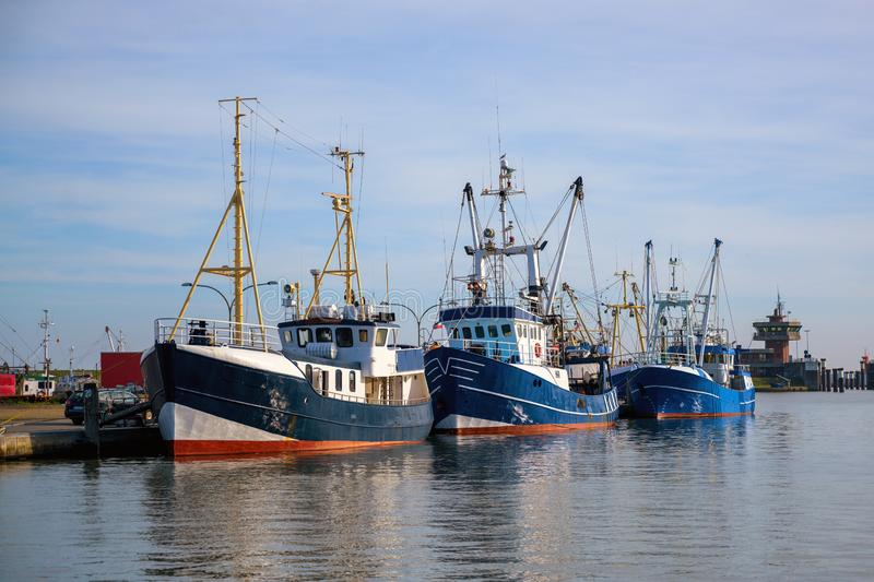 Three blue fishing boats at the quay in the port of Buesum on the North Sea in Germany against the blue sky, copy space. Three blue fishing boats at the quay in stock photography