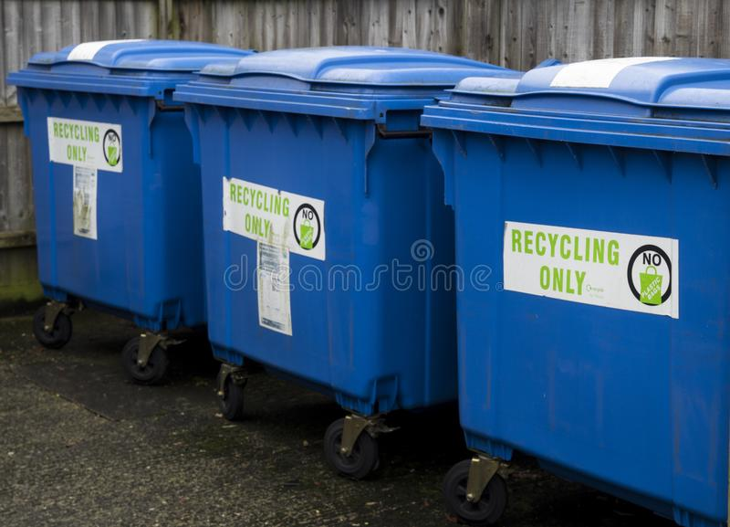 Three blue recycling wheelie bins royalty free stock image