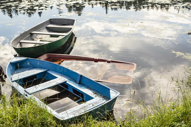 Three boats of different colors are tied at the bank of the river, one of them is sunk, in the countryside, on a summer day royalty free stock image