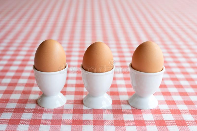 Three boiled eggs in egg cups stock photo