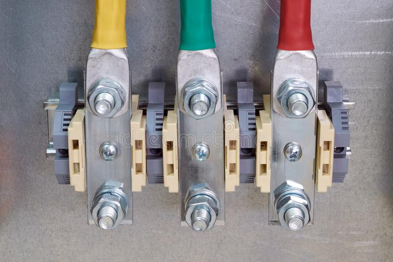 Three bolt-through terminals in the electrical Cabinet. Electrical cables with bolt tips are connected to the terminals. Convenient connection of the stock image