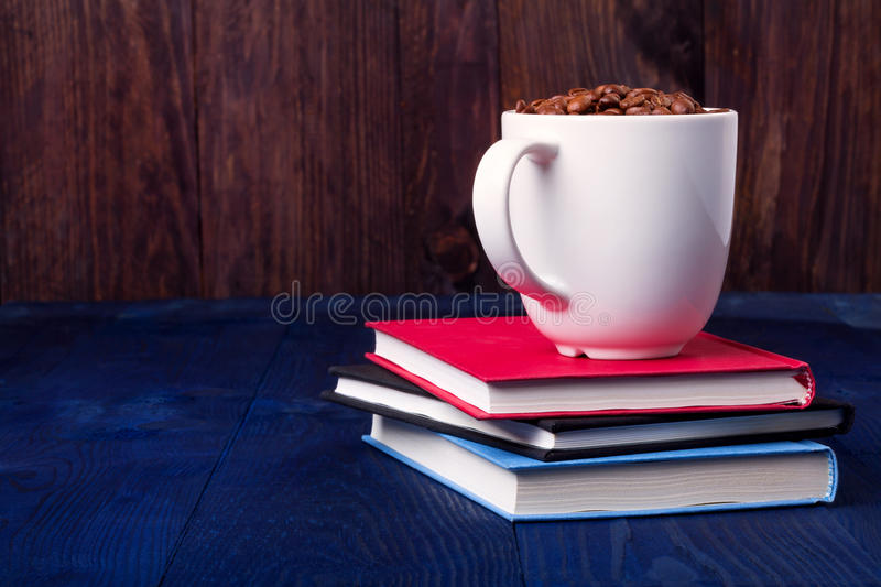 Three books and mug full of coffee beans royalty free stock photography