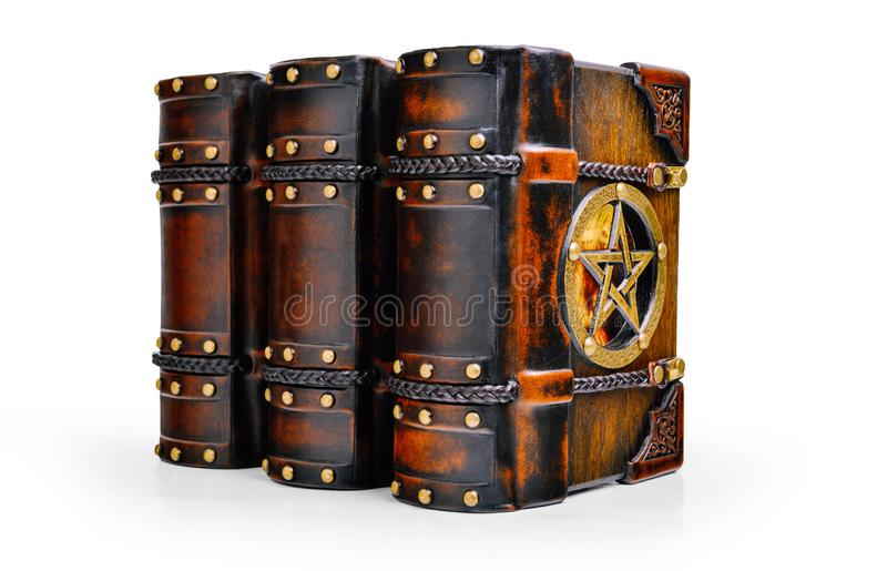 Three books with wooden cover plates, leather corners, locked with braided leather straps and with the pentagram stand up to the t. Able isolated stock photography