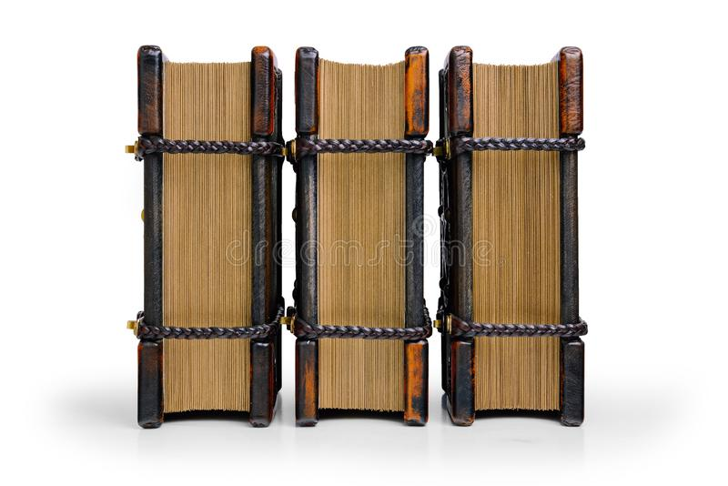 Three books with wooden cover plates and leather corners, locked with braided leather straps stand up to the table isolated with t. He gilded paper end in the stock photo