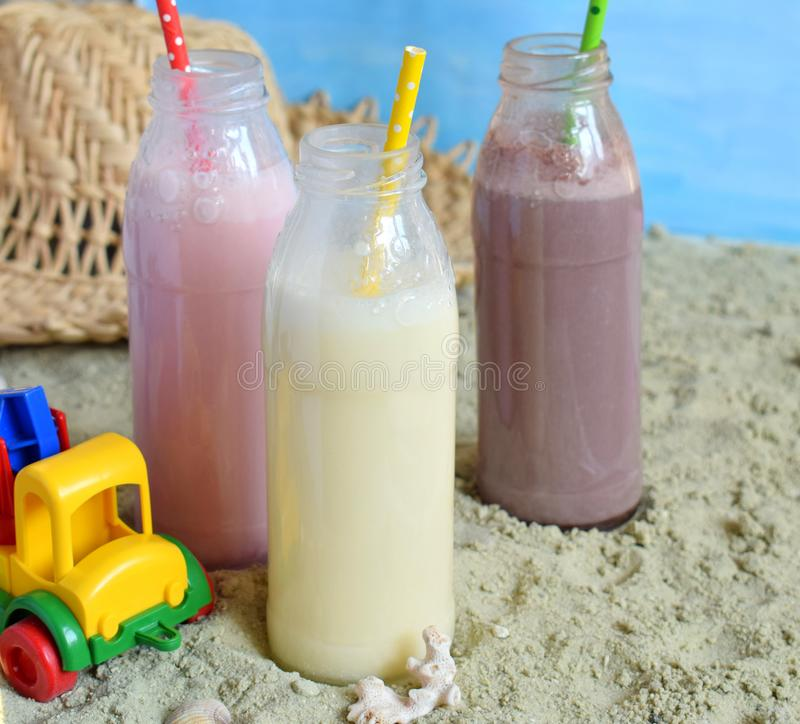 Three bottle of various milkshakes chocolate, strawberry and vanilla . Healthy smoothie with straw. Tasty milk shake cocktails. Re stock photography