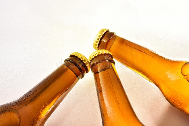Three bottlenecks filled with fresh beer closed on white table royalty free stock images