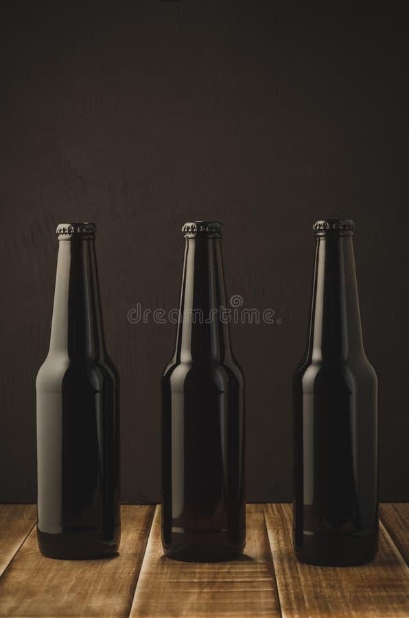 Three bottles of beer on a dark background of a wooden shelf/Three bottles of beer on a dark background of a wooden shelf, royalty free stock image