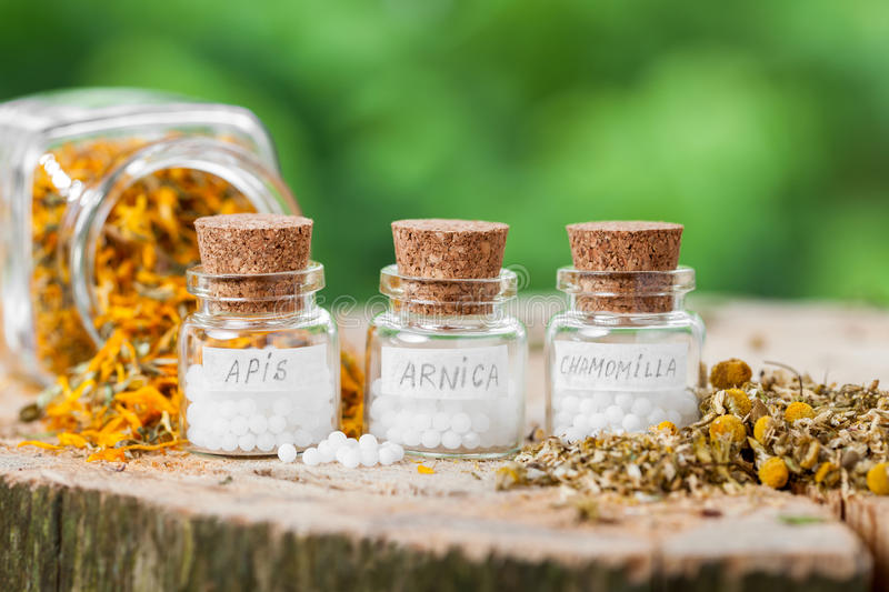 Three bottles of homeopathy globules and healthy herbs. stock photography