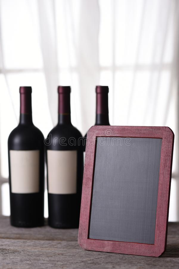 Three bottles of red wine and blank chalk board royalty free stock photos