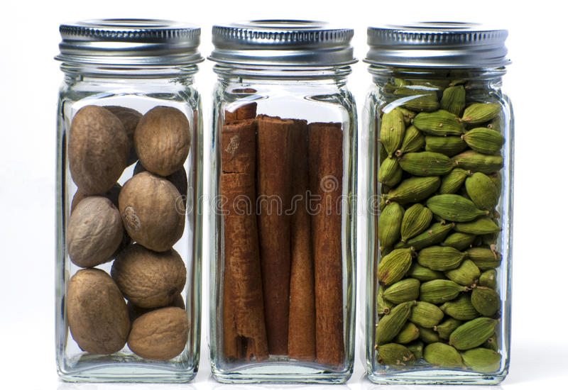 Three bottles of spices. Bottles of organic brown cinnamon, green cardamom and brown nutmeg against a white background stock image