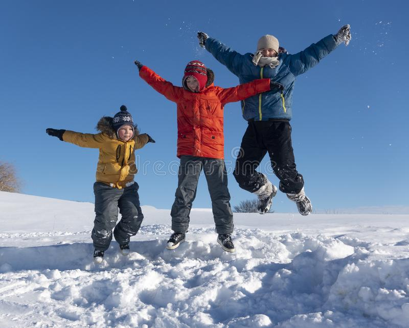 Three boy family friends joyfully jump into the sky over snow drifts in the winter, children play royalty free stock photography