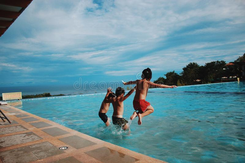 Three Boy's Jumping Into the Water stock images