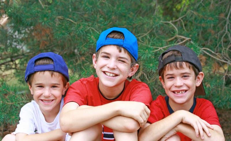 Three Boys in Baseball Hats stock images