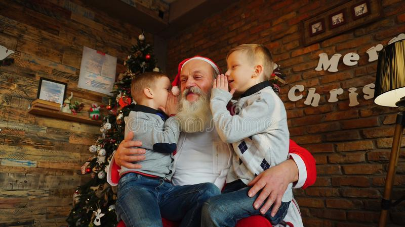 Three boys children keep New Years gifts in their hands and sha. Fervent little boys enthusiastically holding holiday boxes. Three beautiful guys give gifts to stock image