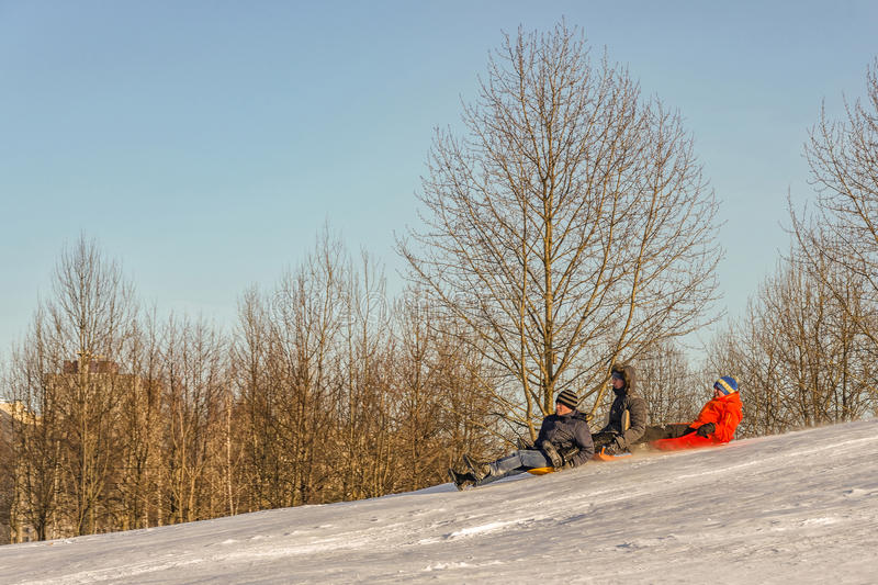The three boys descend from the mountain on a sled stock images