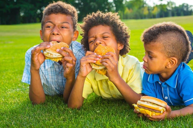 Three boys are eating. royalty free stock photos