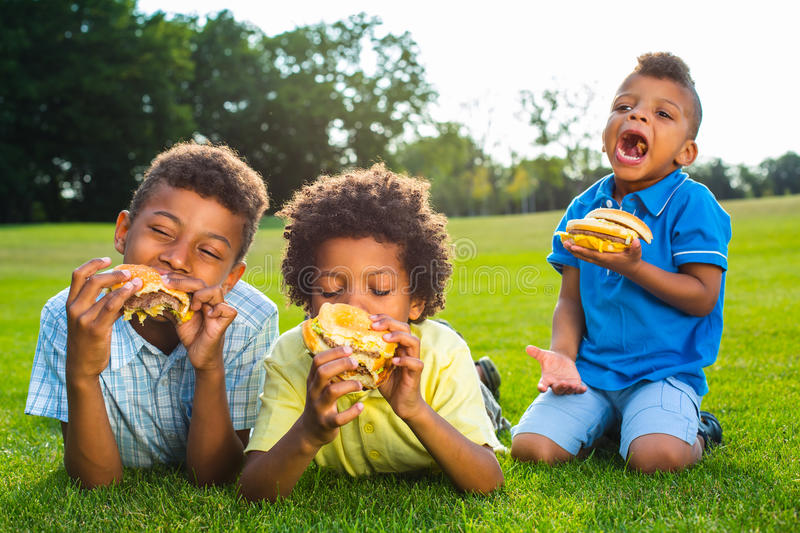 Three boys are eating. stock photography
