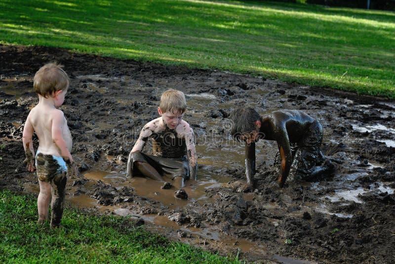 Three boys playing in mud stock photos