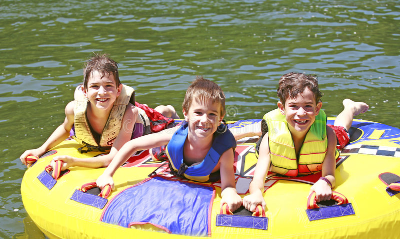 Three Boys Tubing royalty free stock photography