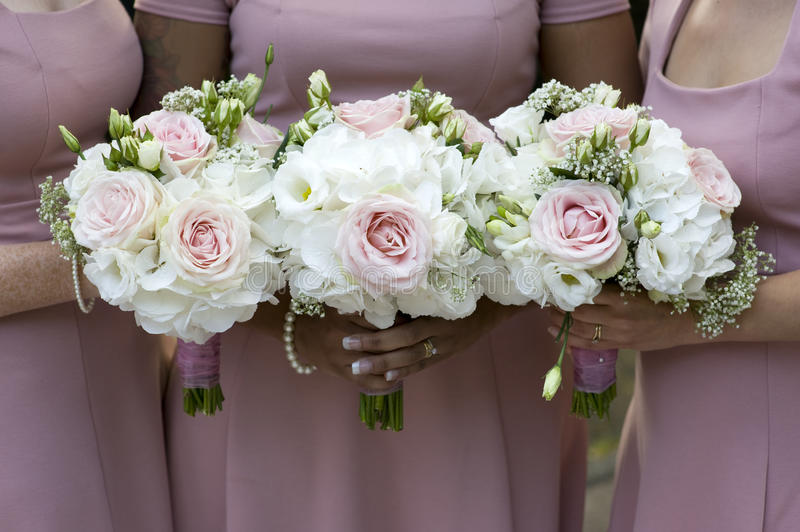 Three bridesmaids holding wedding bouquet. Three bridesmaids in pink dresses holding wedding bouquets of white roses royalty free stock photos