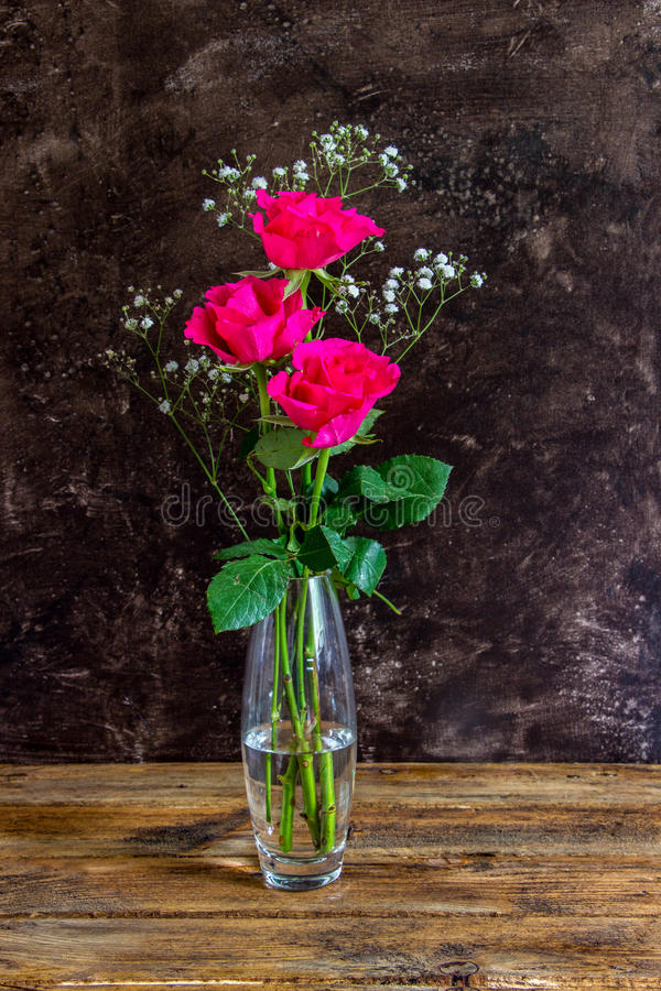 Three bright pink roses. With gypsophila in a crystal vase against a dark background royalty free stock images