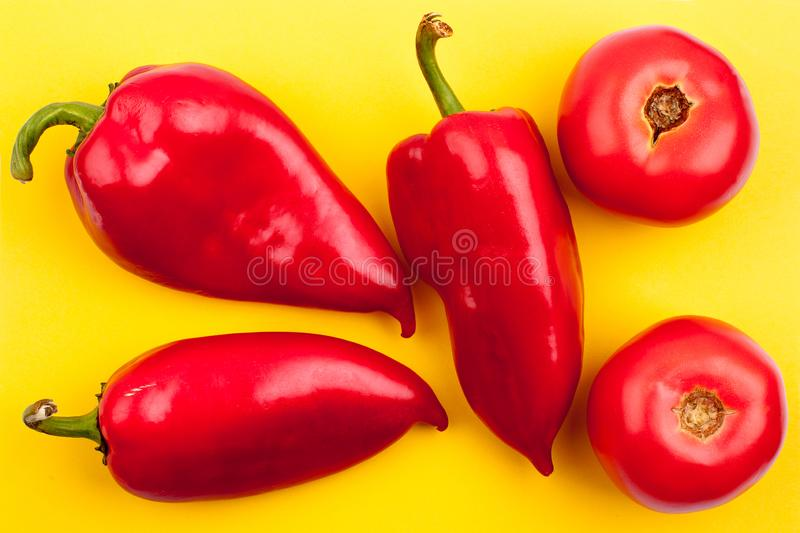 Three bright red peppers and two red tomatoes on yellow background top view close up stock image