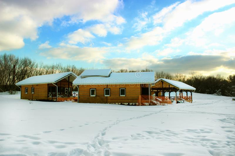 Three bright yellow houses for rest in the middle of a snowy meadow in the forest during the daytime winter.Moscow royalty free stock photography