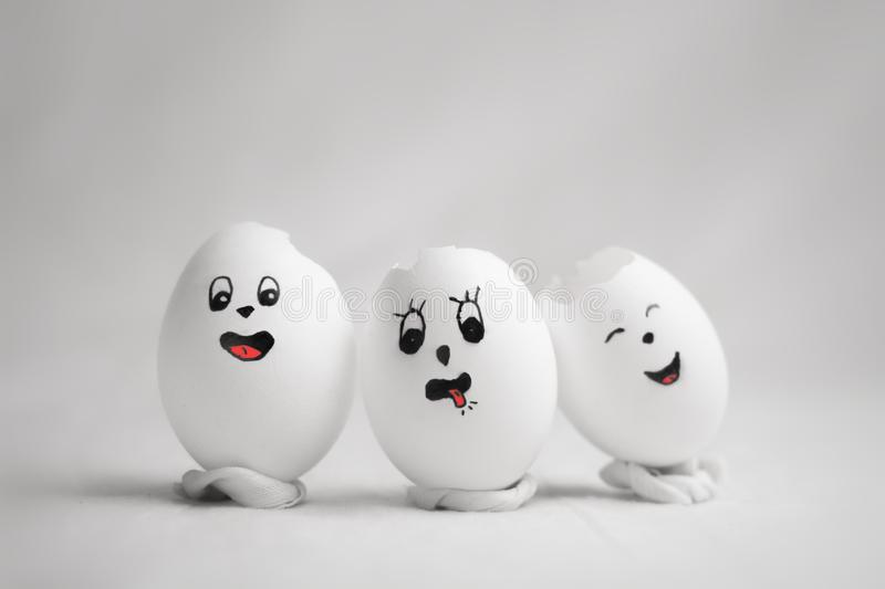 Three broken eggs with funny emoticons. On white background isolated royalty free stock photography