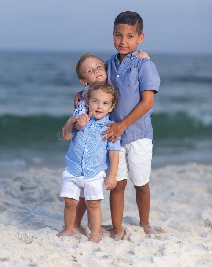 Three brothers embracing one another on a beach stock photo
