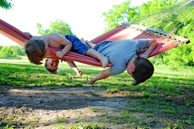 Three brothers playing in hammock royalty free stock photo