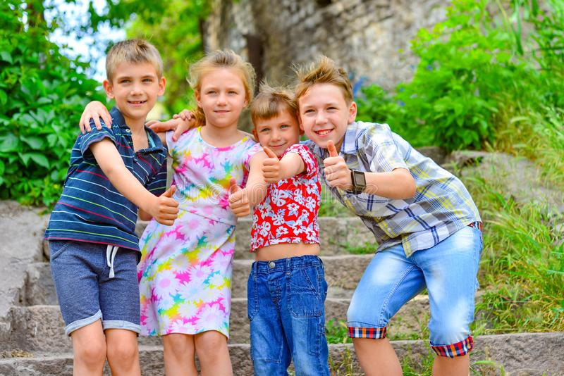 Three brothers and sister stand on the steps in the park and show the class stock photo