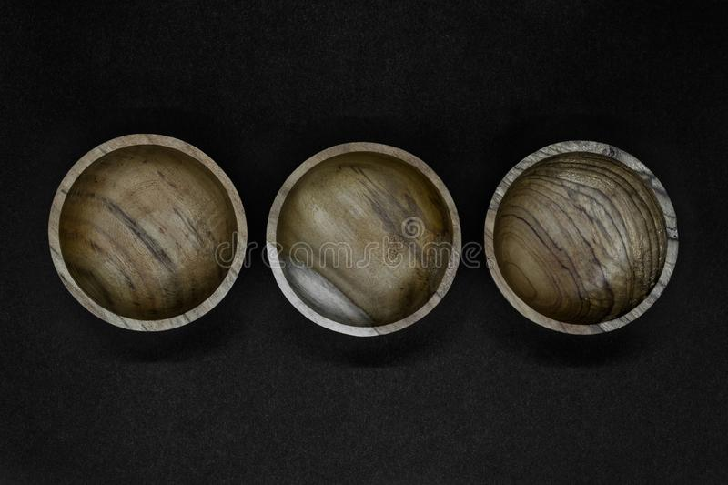 Three brown bowls made from palm tree wood placed in line on black background.  stock photography