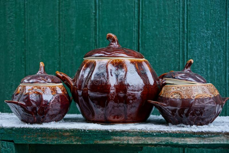 Three brown ceramic pots covered with covers on a table in white snow against a green wall. Three brown ceramic pots covered with covers on a table in white snow royalty free stock images