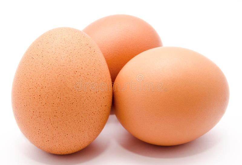 Three brown chicken eggs isolated on a white background royalty free stock photography