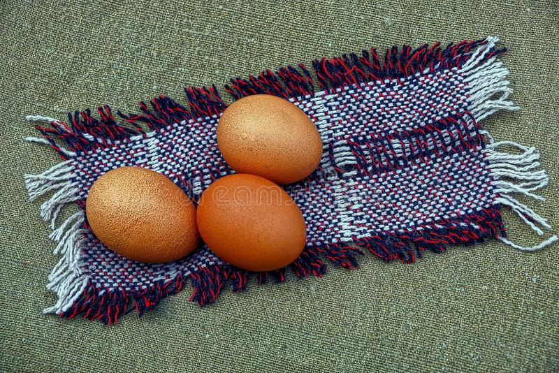 Three brown chicken eggs lie on a colored wool napkin stock photography