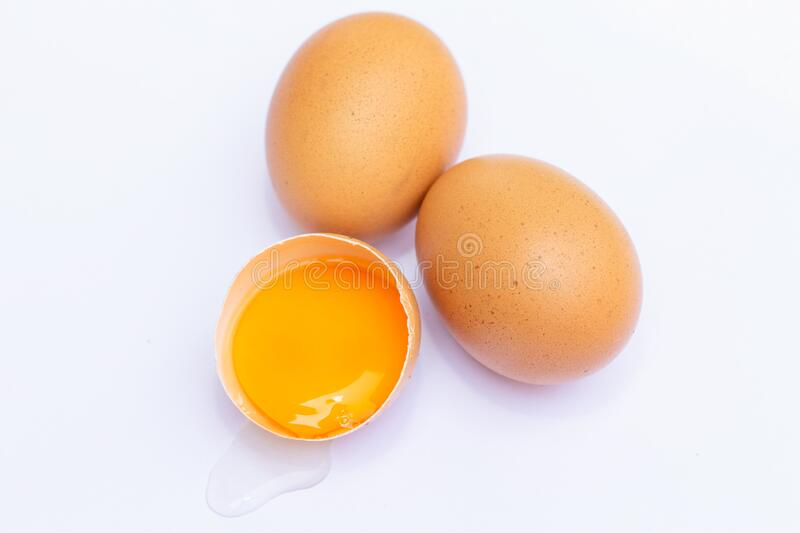 Three brown eggs With one egg broken in half, with a yolk inside the eggshell, laid on a white background stock photos
