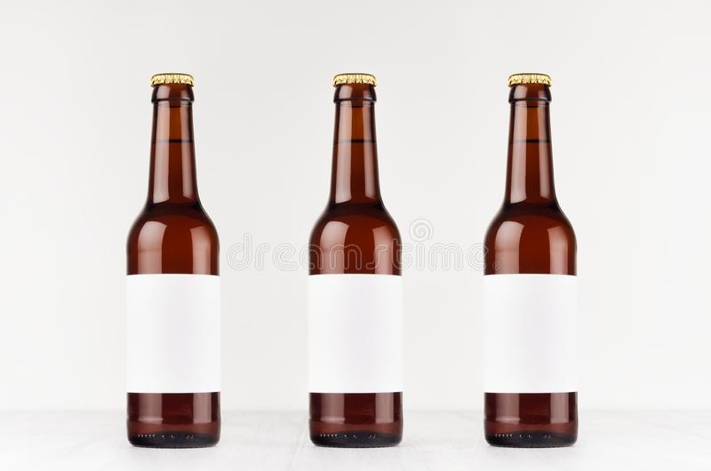 Three brown longneck beer bottles 330ml with blank white label on white wooden board, mock up. royalty free stock photo