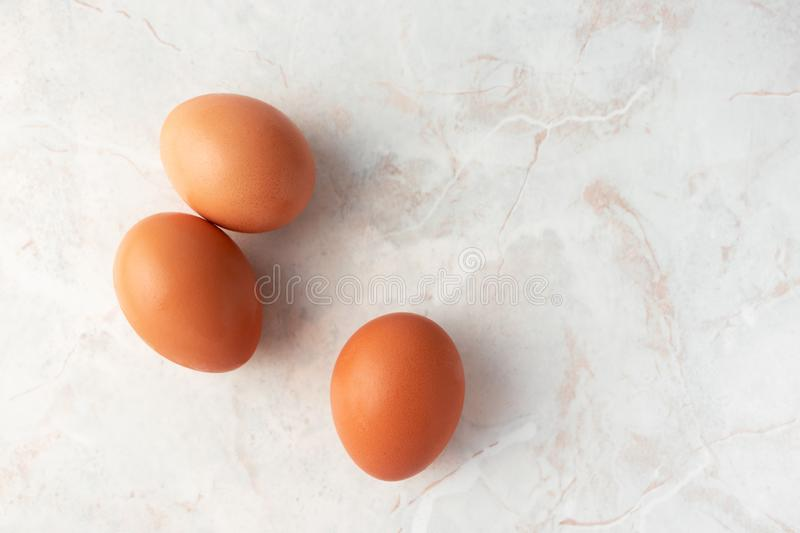 Three brown organic eggs on marble background, top view. Chicken free-range eggs royalty free stock photo