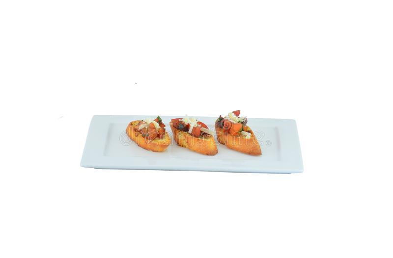 Three bruschettes with tomato cheese and herbs and garlic served stock photo