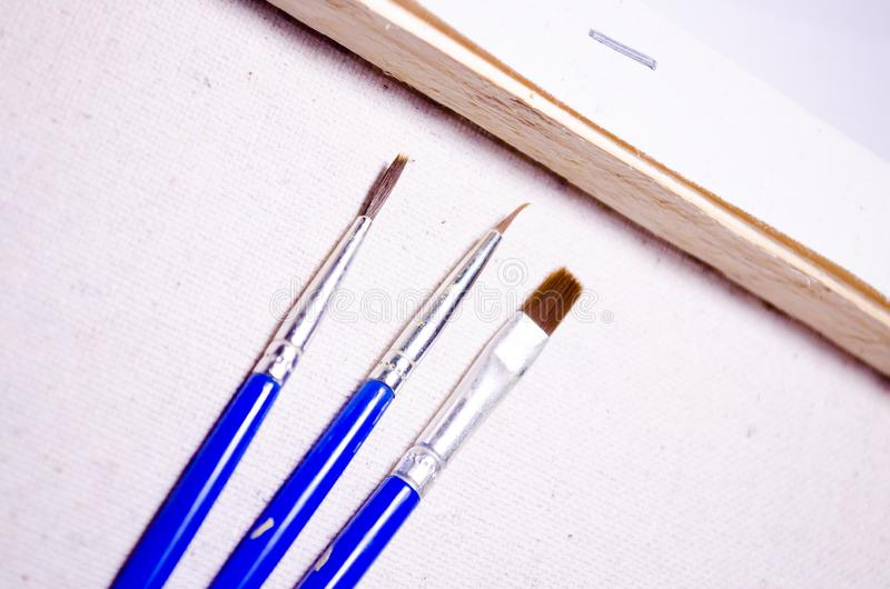 Three brushes. Drawing set. Stretcher. Canvas. Tree. stock image