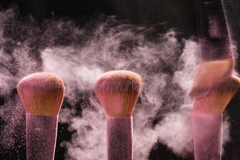 Three brushes for makeup with pink make-up mineral powder in motion on a black background stock images
